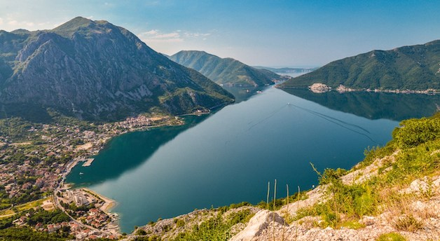 This is a photo of the Bay of Kotor with mountains, sea, and a town.