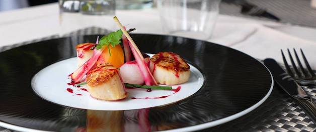 This is a picture of a gourmet dish of sea scallops with lemongrass on a black and white plate.